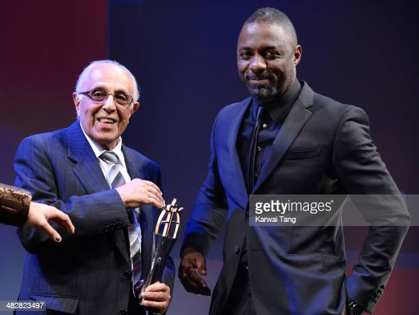Idris Elba presents Ahmed Kathrada who was imprisoned on Robben Island with Nelson Mandela from 19641989 with the Founders Award during The Asian...