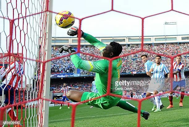 Idriss Kameni of Malaga CF fails to stop Tiago Mendes of Club Atletico de Madrid scoring his team's opening goal during the La Liga match between...