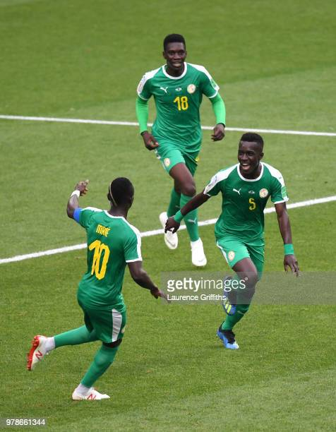 Idrissa Gana Gueye of Senegal celebrates with Sadio Mane and Ismaila Sarr of Senegal after Thiago Cionek of Poland scored and own goal to put Senegal...