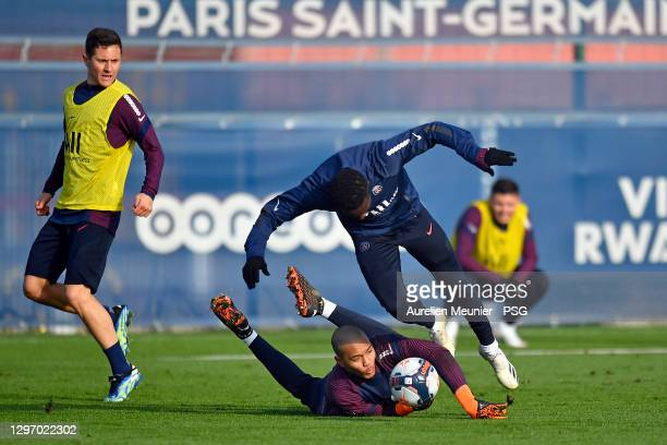 Idrissa Gueye is tackled by teammate Mathyas Randriamamy during a Paris Saint-Germain training session at Ooredoo Center on January 18, 2021 in...