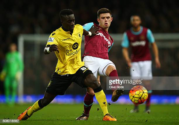 Idrissa Gueye of Aston Villa and Aaron Cresswell of West Ham United compete for the ball during the Barclays Premier League match between West Ham...