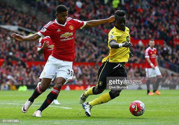 Idrissa Gueye of Aston Villa is closed down by Marcus Rashford of Manchester United during the Barclays Premier League match between Manchester...