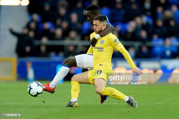 Idrissa Gueye of Everton and Eden Hazard challenge for the ball during the Premier League match between Everton and Chelsea at Goodison Park on March...