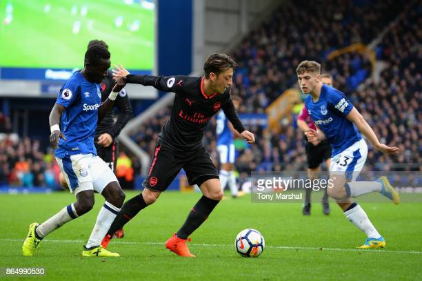 Idrissa Gueye of Everton and Mesut Ozil of Arsenal battle for possession during the Premier League match between Everton and Arsenal at Goodison Park...