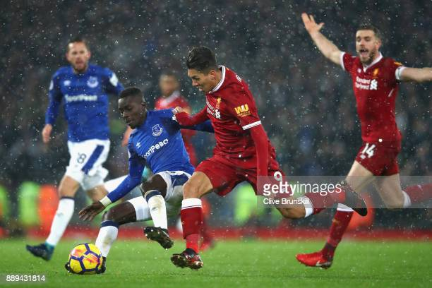 Idrissa Gueye of Everton and Roberto Firmino of Liverpool battle for possession during the Premier League match between Liverpool and Everton at...