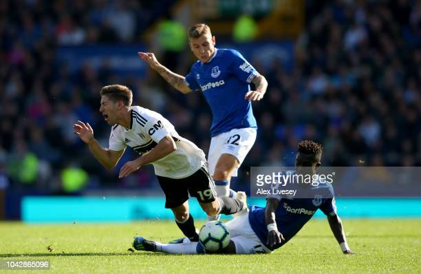 Idrissa Gueye of Everton slides in to tackle Luciano Vietto of Fulham as Lucas Digne of Everton looks on during the Premier League match between...