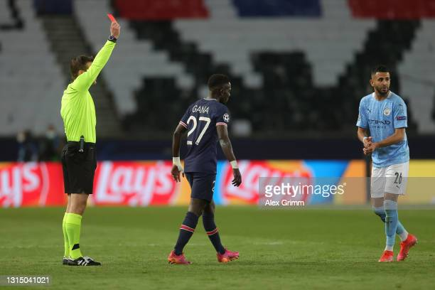 Idrissa Gueye of Paris Saint-Germain is shown a red card by Referee Felix Brych during the UEFA Champions League Semi Final First Leg match between...