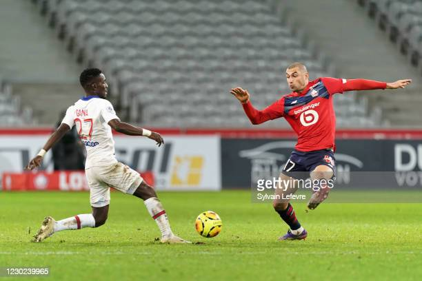 Idrissa Gueye of Paris SG is challenged by Burak Yilmaz of Lille OSC during the Ligue 1 match between Lille OSC and Paris Saint-Germain at Stade...
