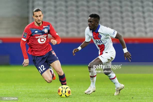 Idrissa Gueye of Paris SG is challenged by Yusuf Yazici of Lille OSC during the Ligue 1 match between Lille OSC and Paris Saint-Germain at Stade...