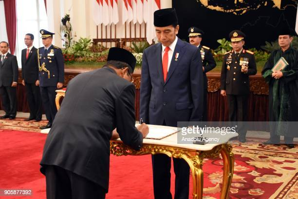 Idrus Marham signs document of appointment as he is flanked by President Joko Widodo during an inauguration ceremony at the State Palace in Jakarta...