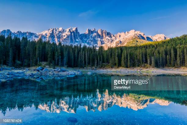 idyllic blue alpine lake carezza, dolomites, italian tirol alps - alta badia stock pictures, royalty-free photos & images