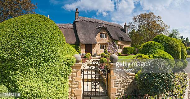 Idilliaci cottage di campagna tetto di paglia bella Estate gardens Cotswolds Regno Unito