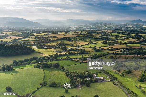 Idyllic country meadows misty mountains aerial landscape