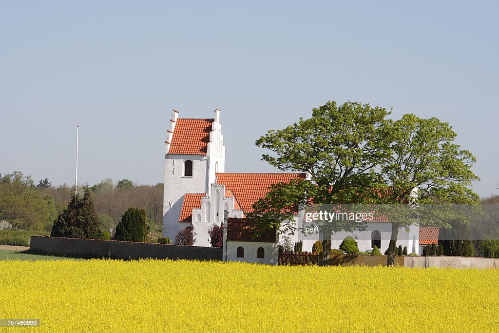 Idyllic country side parish church behind oilseed rape field : Stock Photo