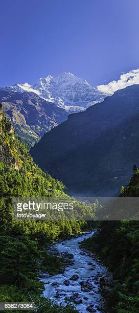 Idyllic mountain valley snowy peaks overlooking Sherpa village Himalayas Nepal