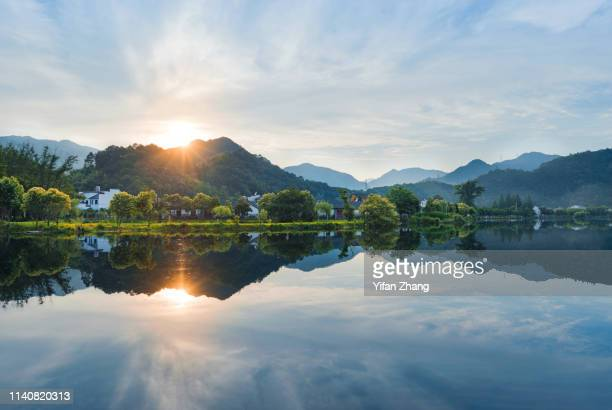 idyllic mountain village reflection under sunset - lago - fotografias e filmes do acervo