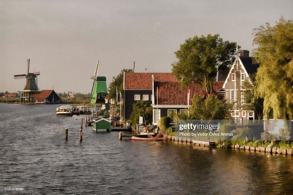 idyllic quintessential Dutch landscape on the banks of the river Zaan with wooden windmills and traditional wooden houses and boats in Zaanse Schans, Netherlands : Foto de stock