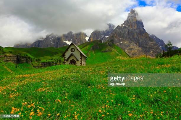 idyllic rolle pass, chapel and pale di san martino pinnacle snowcapped mountain range at springtime - trento foto e immagini stock