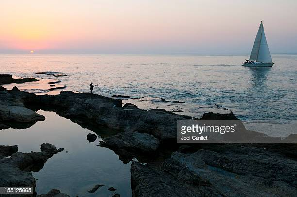 sunset fisherman and sailboat in beirut, lebanon - lebanon stock pictures, royalty-free photos & images