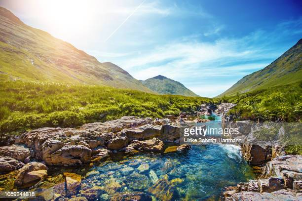 idyllic scene with mountains and stream in scottish highlands near glen coe - grampian scotland stock pictures, royalty-free photos & images