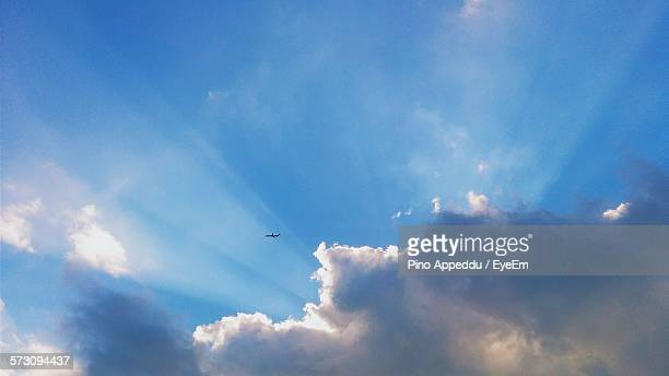 Idyllic Shot Of Airplane Flying By Clouds In Sky With Sunbeam