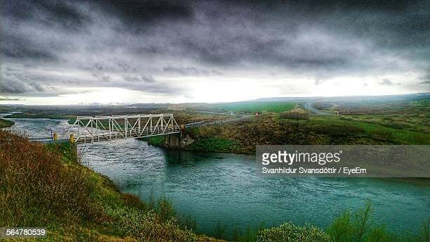 Idyllic Shot Of Bridge Over River Against Storm Cloud Sky In Selfoss