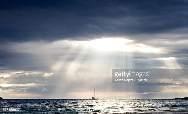 Idyllic Shot Of Cloudy Sky With Sunbeam Over Sailboat In Sea
