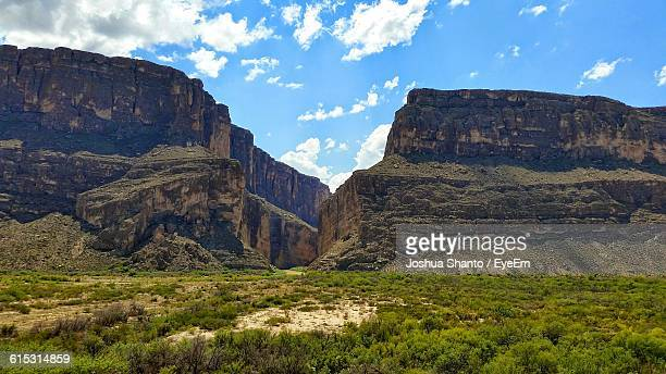idyllic shot of green landscape and rocky mountains against sky - big bend national park stock pictures, royalty-free photos & images