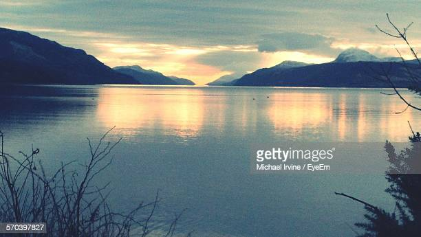 idyllic shot of loch ness by mountain range against sunset sky - loch ness stock photos and pictures