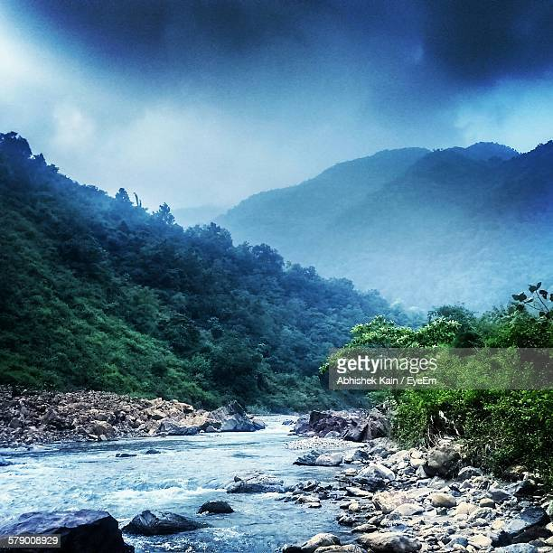 Idyllic Shot Of River Stream By Mountain Range Against Sky