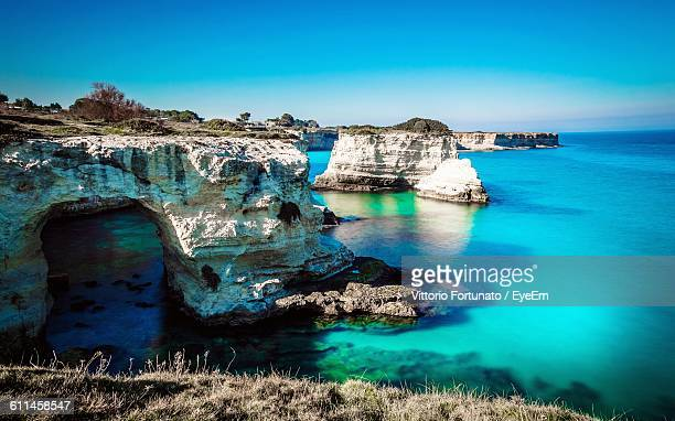 Idyllic Shot Of Rock Formation In Sea At Salento Against Sky