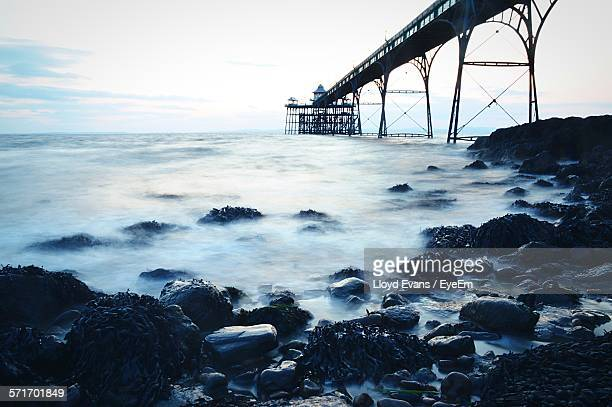 idyllic shot of rocky coast by clevedon pier against sky - clevedon pier stock pictures, royalty-free photos & images