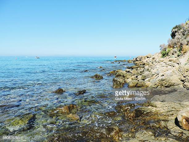 Idyllic Shot Of Rocky Coastline By Sea Against Sky