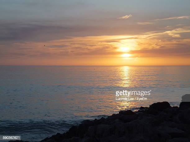 idyllic shot of silhouette rocks in sea against sunset sky - lucinda lee stock photos and pictures