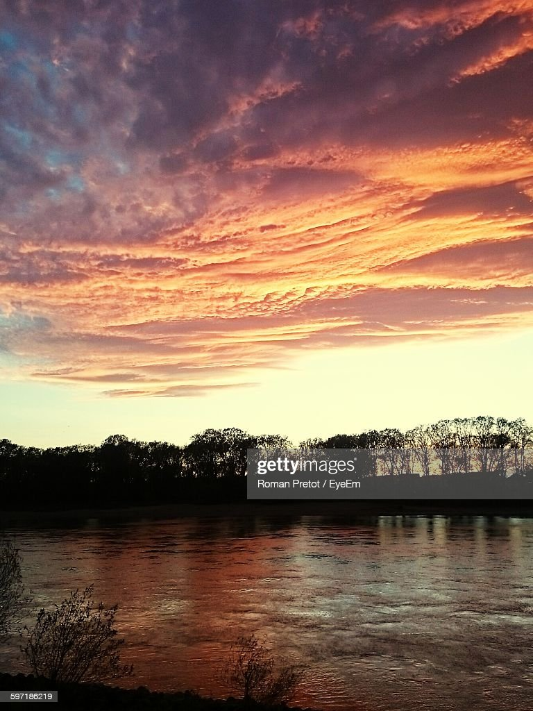 Idyllic Shot Of Silhouette Trees By River Against Cloudy Sunset Sky : Stock-Foto