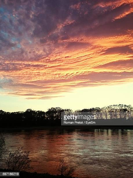 idyllic shot of silhouette trees by river against cloudy sunset sky - roman pretot stock-fotos und bilder