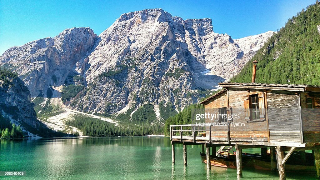 Idyllic Shot Of Stilt House In Pragser Wildsee By Rocky Mountains Against Sky : Stock Photo
