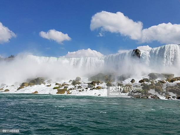 idyllic shot of waterfall in sea against sky - nissan stock pictures, royalty-free photos & images
