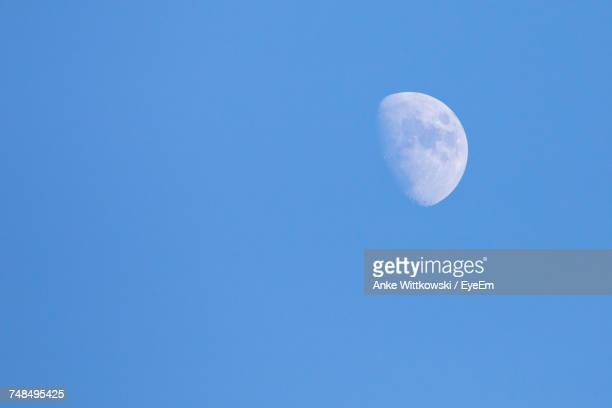 Idyllic Shot Of Waxing Moon Against Clear Blue Sky