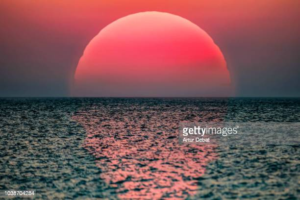 idyllic sunrise with huge sun rising over the sea. - zonsopgang stockfoto's en -beelden