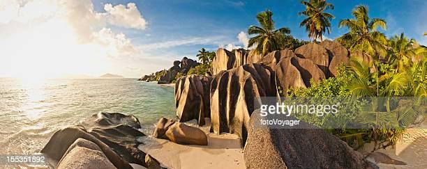 Idyllic tropical island beach sunset palm trees panorama