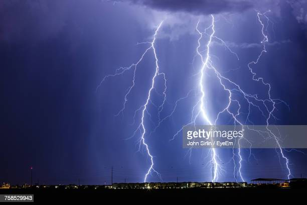 idyllic view of lightning over landscape at night - extreme weather stock photos and pictures