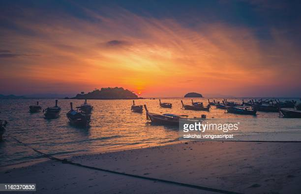 idyllic view of longtail boats on beach against sky during sunrise at koh lipe island, thailand, asia - インド洋 ストックフォトと画像