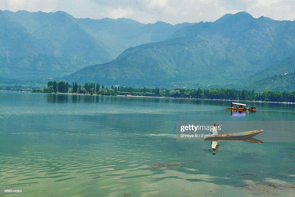 Idyllic View Of Man Rowing Boat On Lake Against Mountains : Stock Photo