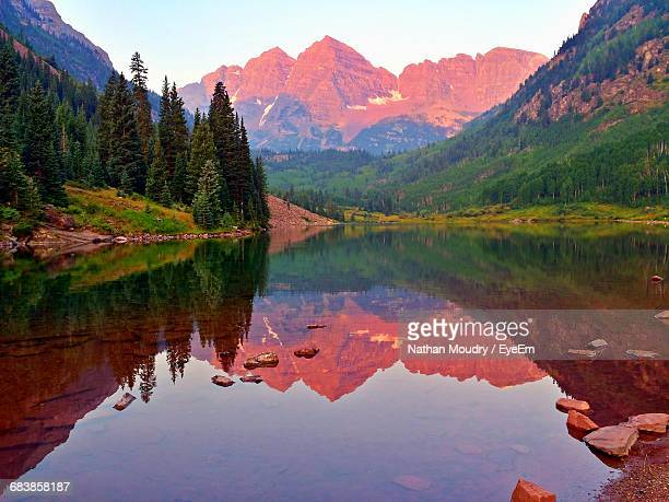 idyllic view of maroon bells by calm lake - maroon bells stock photos and pictures