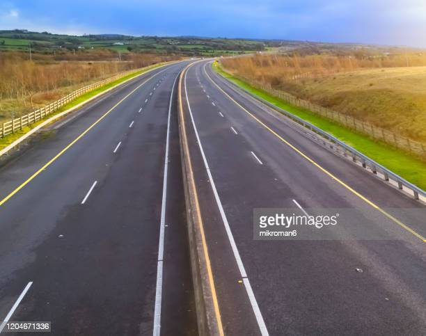 idyllic view of multiple lane highway by sunset time - road stock pictures, royalty-free photos & images