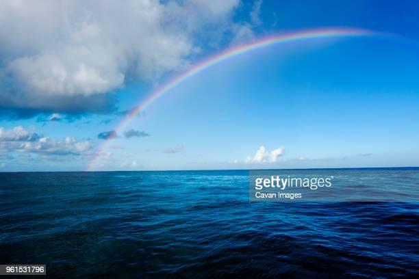idyllic view of rainbow over sea - 虹 ストックフォトと画像