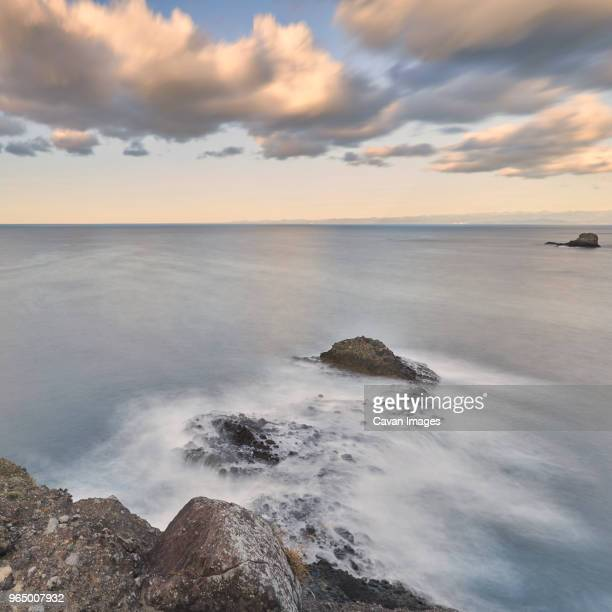 Idyllic view of sea against cloudy sky