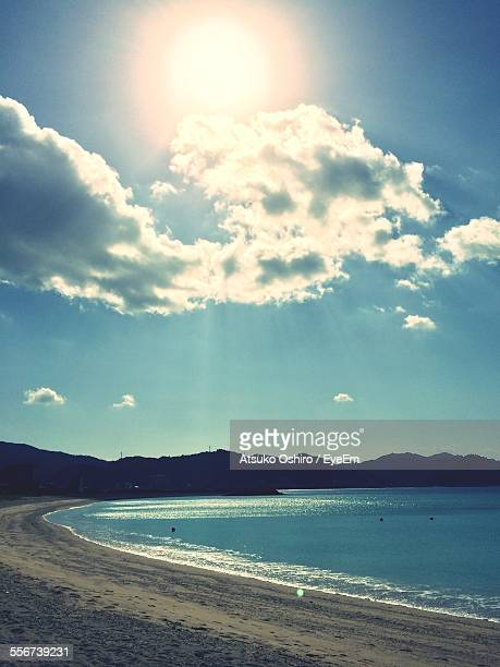 Idyllic View Of Sea, Hills And Sandy Beach, Sun And Clouds In Blue Sky