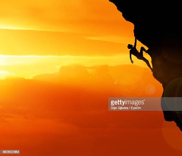 Idyllic View Of Silhouette Man Rock Climbing Against Orange Sunset Sky